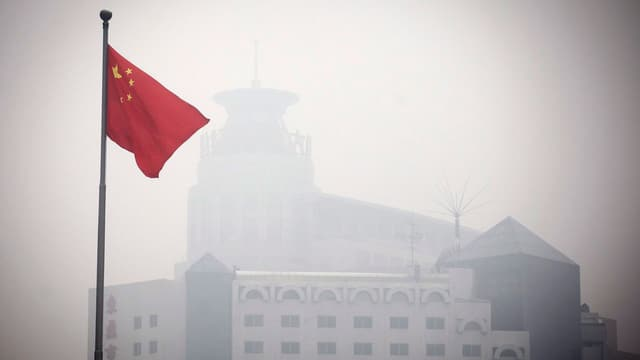 Chinesische Flagge vor einem Gebäude in Peking, das durch den Smog kaum sichtbar ist.