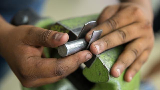 Ein Flüchtling arbeitet an einem Schraubstock.