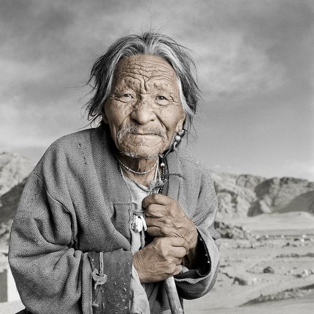 Ein älterer Mann blickt in die Kamera. Er stützt sich auf einen Holzstock.