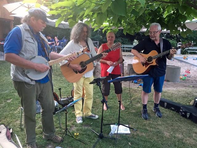 Vier Personen mit Musikinstrumenten und Noten