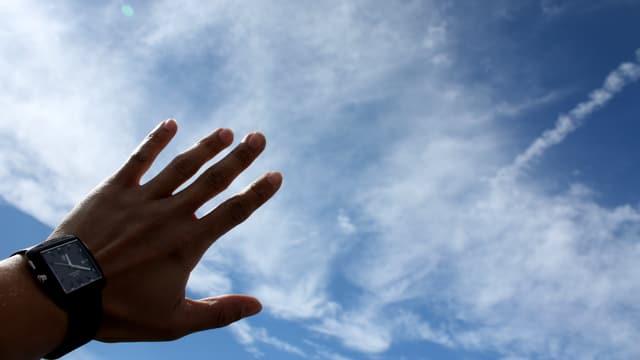 Eine Hand vor Wolken gehalten