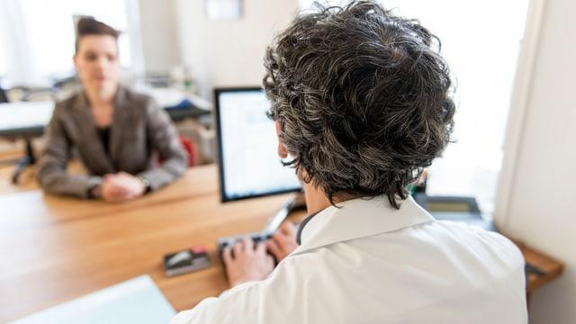 Ein Arzt von hinten am Computer an einem Pult, eine Frau sitzt ihm gegenüber.
