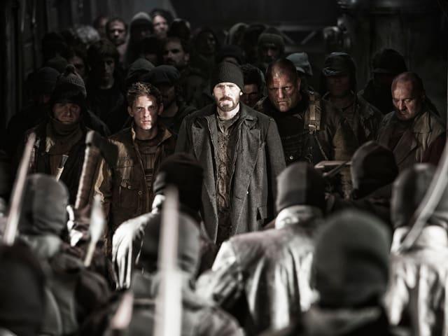 Evans steht in schwarzem Mantel vor einer Gruppe von ebenfalls dunkel gekleideten Menschen. Ihnen gegenüber stehen Soldaten.