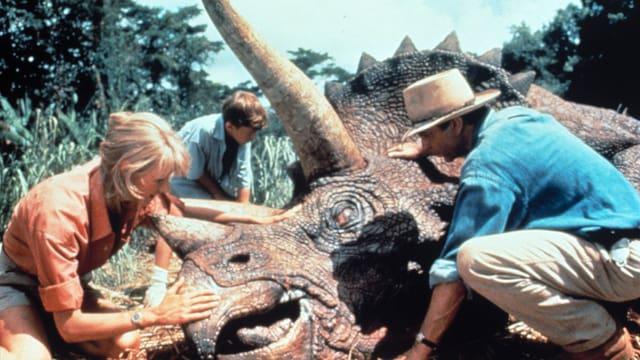 Ein Dinosaurier liegt am Boden, ein Mann, eine Frau und ein Junge stehen um ihn herum und streicheln ihm den Kopf.