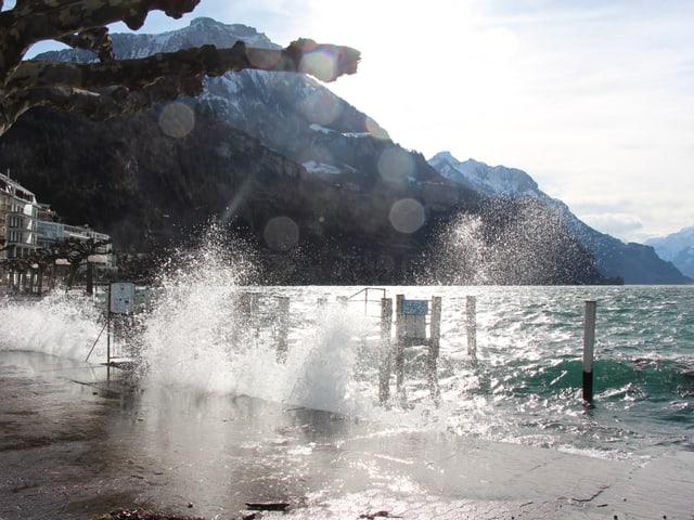 An der Uferpromenade von Brunnen SZ brechen die Wellen. Durch das Föhnfenster am Himmel scheint die Sonne.