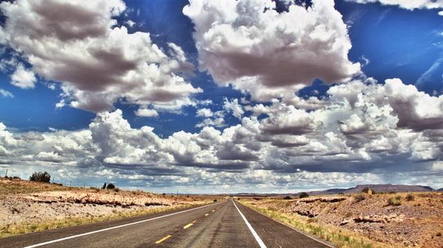Ein Highway in der Wüste unter dramatischen Wolken.