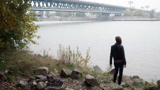 Eine Frau steht neben einer Brücke am Ufer eines breiten Flusses.