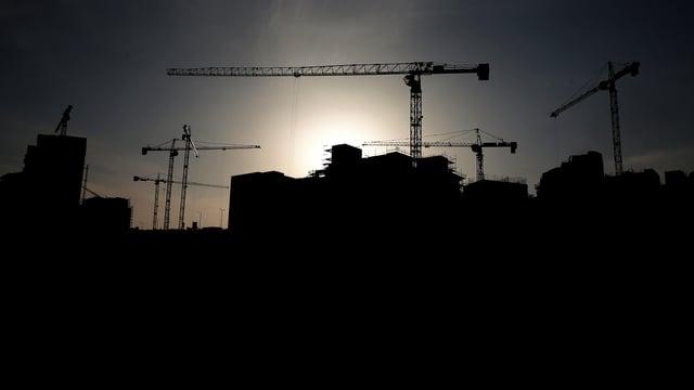 Silhouetten von Gebäuden und Baukränen.