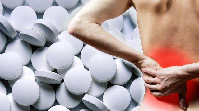 Person hält sich schmerzenden Rücken, im Hintergrund ein Haufen Tabletten.