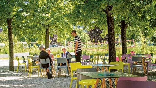 Menschen sitzen in einem grünen Park mit Tischen und Bäumen in Sitten.