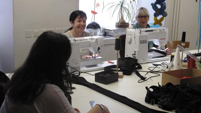 Zwei Frauen arbeiten an Nähmaschinen und schauen in die Kamera.