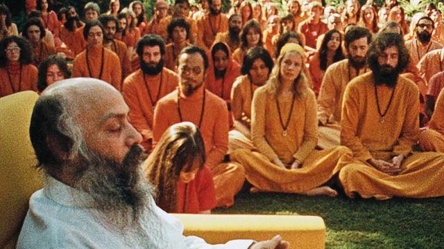 Ein älterer Mann sitzt in einem weissen Kittel sitzt vor einer grossen Menschenmenge in orangen Gewändern.