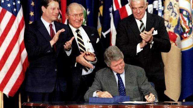 Bill Clinton unterzeichnet ein Abkommen, hinter ihm Vize-Präsident Al Gore und zwei andere Männer.