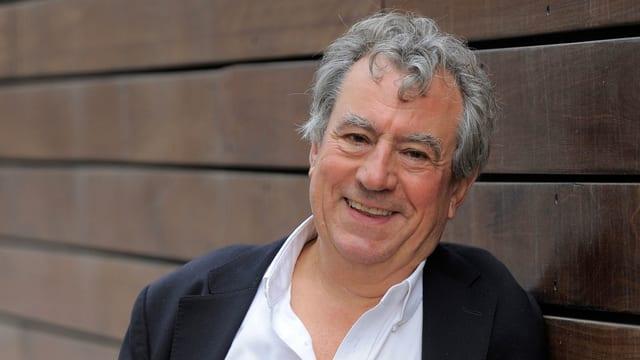 Lächelnd gegen eine Holzwand gelehnt: Monty Python-Star Terry Jones.