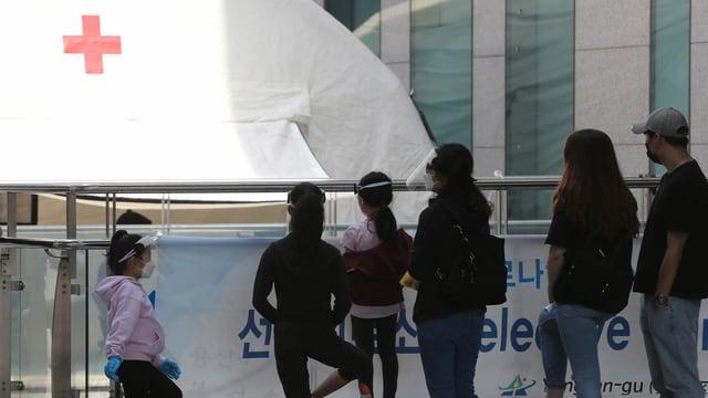 Personen warten vor einem Zelt mit Rotkreuzsymbol.