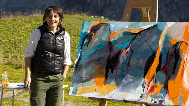Eine Künstlerin steht neben einer Staffelei.