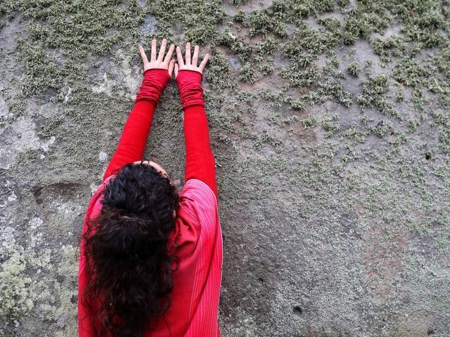 Frau legt flache Hände auf Stein