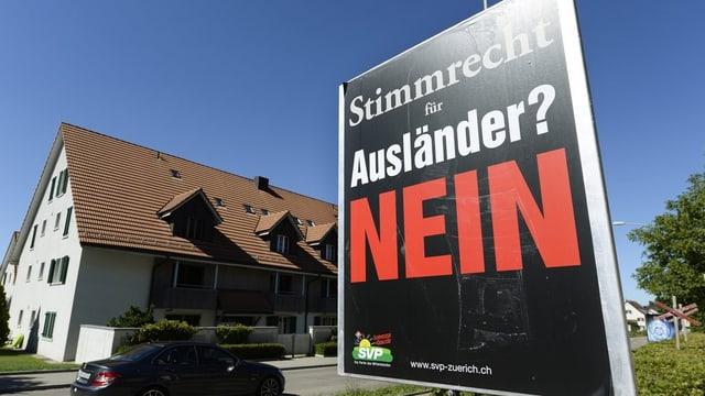 """Abstimmungsplakat der SVP am Strassenrand mit der Parole """"Stimmrecht für Ausländer NEIN"""""""