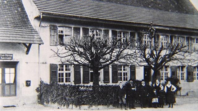 Schwarzweiss-Foto eines Landgasthofes, mit Personen im Vordergrund.