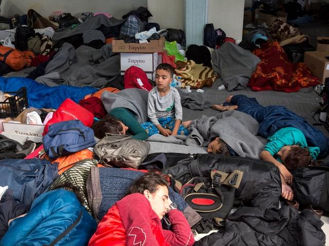 Ein Knabe sitzt in einer Halle - einem chaotischen Platz, rundum schlafen Leute. Es hat viele Taschen, die rumliegen.