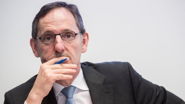 Mann mit dunken kurzen Haaren und Brille schaut in die Ferne