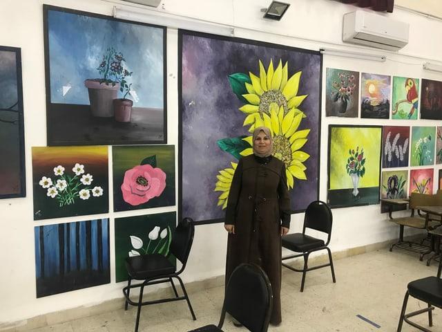 Bild einer Rektorin einer sanierten Mädchenschule steht vor bebilderter Wand