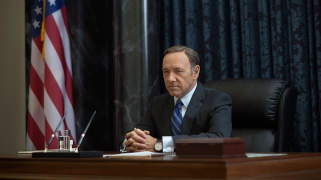 Ein Mann sitzt in einem Chefsessel am Tisch, dahinter ist eine Amerika-Flagge zu sehen.
