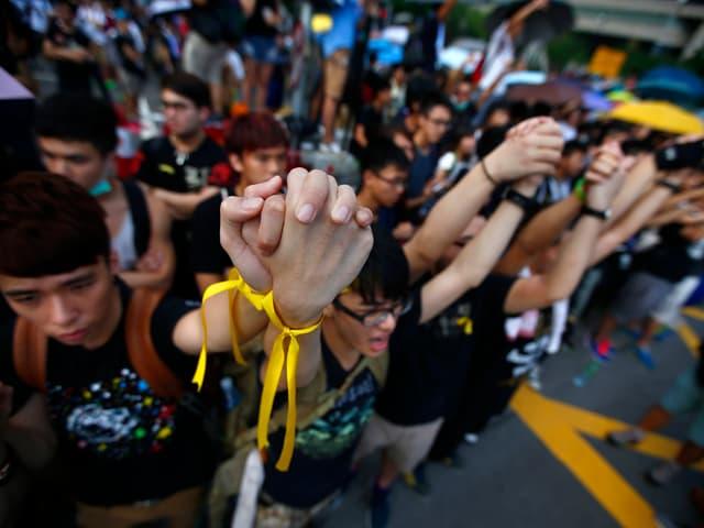 Demonstranten halten gemeinsam die Hände in die Höhe