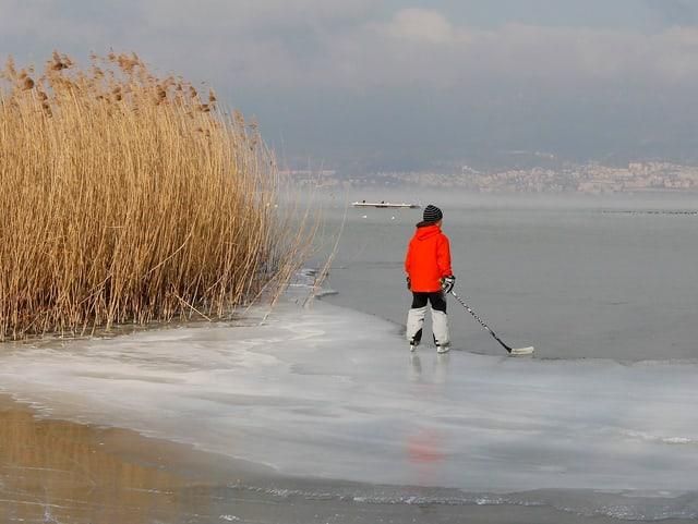 Ein Kind steht mit Schlittschuhen und Hockeyschläger auf dem gefrorenen See.