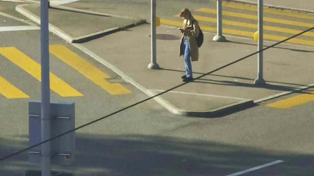 Strassenkreuzung, an der eine junge Frau alleine steht.