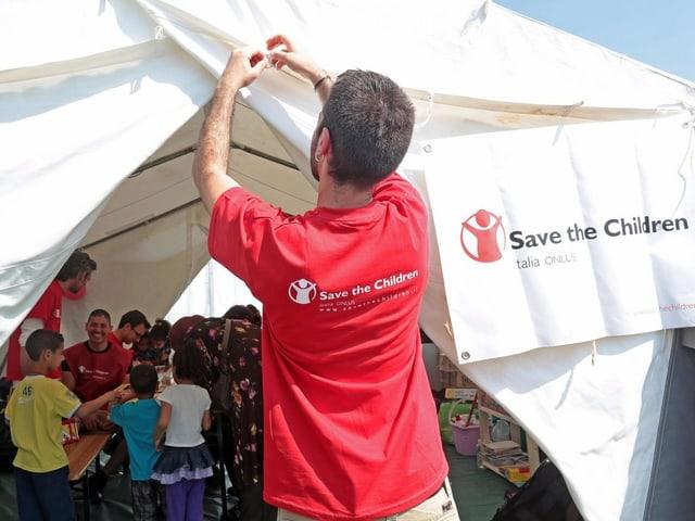 Helfer vor Zelt mit Kindern.
