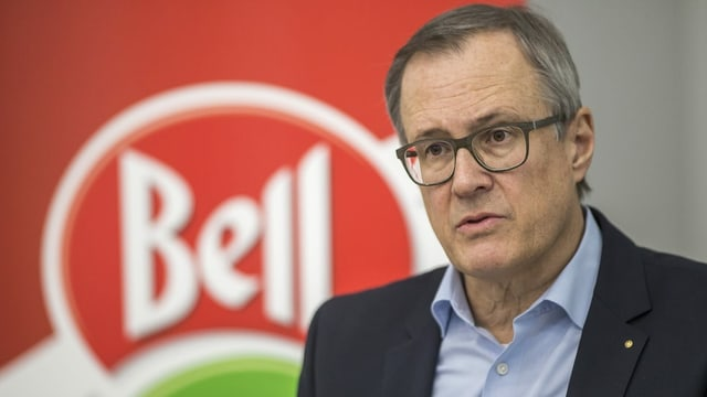 Mann vor rotem Bell Logo