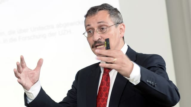 Ein Mann mit Brille und Schnauz spricht zu einem Publikum.