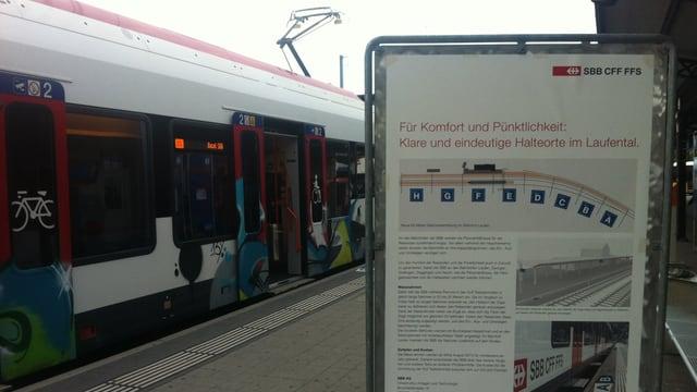 Ein Informationsplakat über das neue System. Dahinter ein Zug, der im Bahnhof Laufen hält.