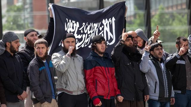 Salafisten demonstrieren, zu sehen auch eine schwarze Fahne mit weisser, arabischer Schrift.