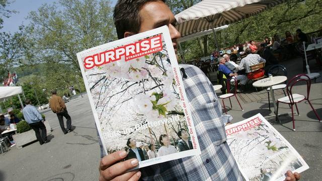 Ein Strassenverkäufer hält ein Strassenmagazin Surprise in die Höhe und preist es zum Verkauf an.