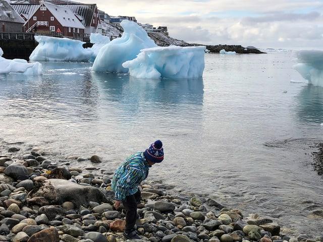 Ein Bub mit Strickmütze am Ufer, Eisberge