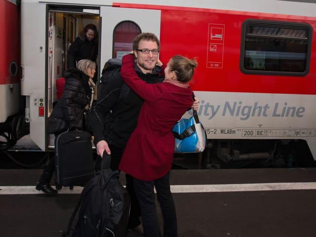 Marco Weber an einem Schweizr Bahnhof wird von einer blonden Frau umarmt.