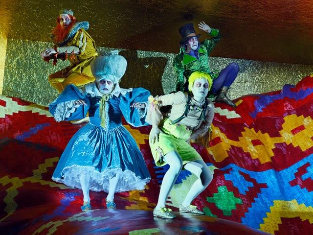 Vier Schauspieler in bunten Kostümen, mit weisser Schminke und roten umrandeten Augen.