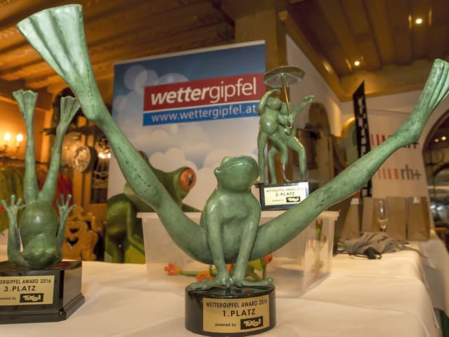 Die Siegerpokal als stilisierrte Froschskulpturen in verschieden Posen. Im Sprung, auf dem Rücken und zu zweit unter einem Schirm.