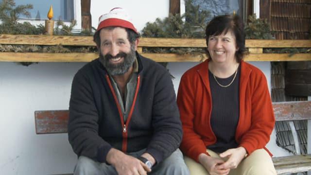 Ein bärtiger Mann und eine Frau sitzen auf einem Bank.