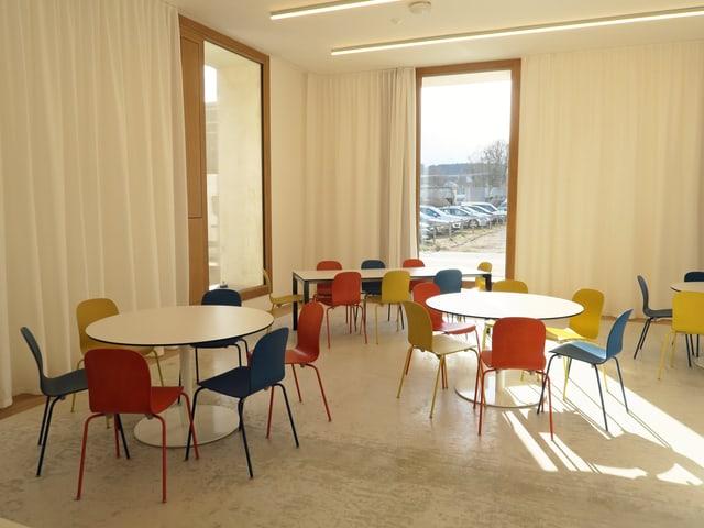 In einem hellen Raum stehen moderne Tische und Stühle.