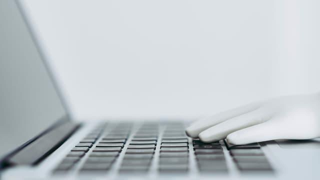 Notebook mit Roboterhand auf der Tastatur
