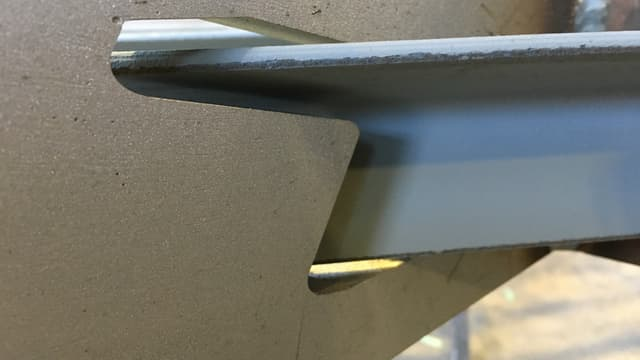 Ein Metallwinkel, der durch anderes Stahlteil führt.