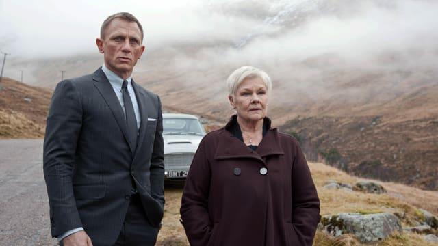 Ein Mann im Anzug und eine ältere Frau im Mantel stehen vor einem Auto in einer nebligen Landschaft.
