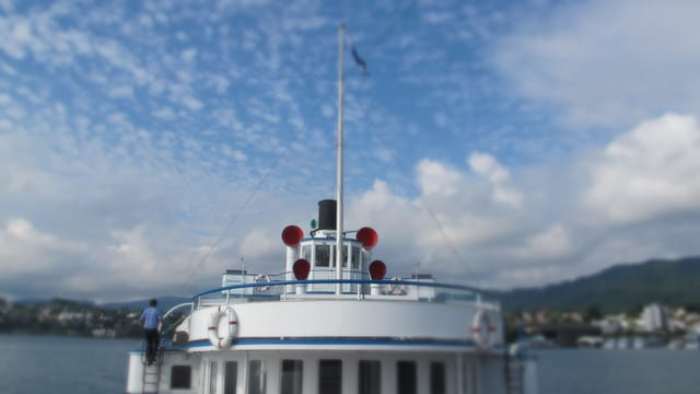 Ein Schiff fährt auf dem See unter blauem Himmel.