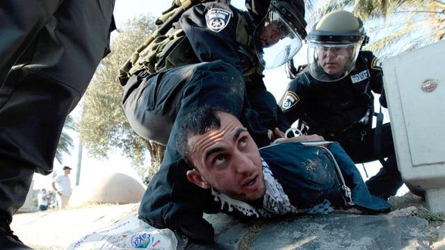 Ein arabischer Mann wird von der Polizei zu Boden gedrückt.