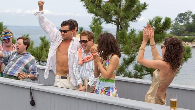 DiCaprio mit offenem Hemd, geballter Siegerfaust umgeben von Sekt, Bikini-Damen und Buddies.