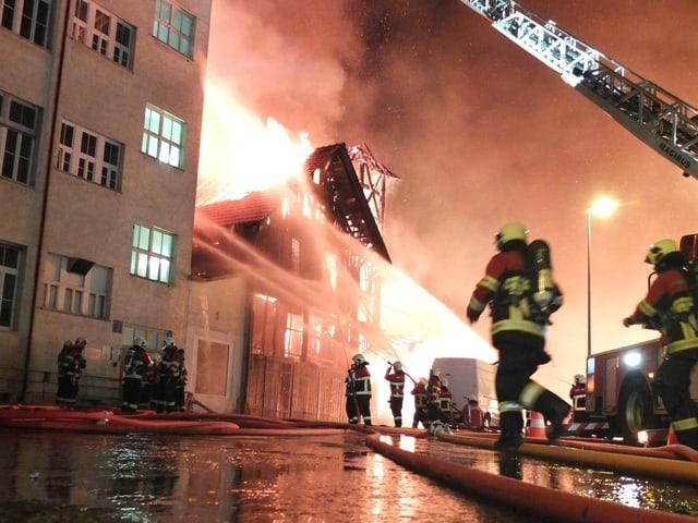 Feuerwehrleute rennen umher, im Hintergrund ein grosses Gebäude in Vollbrand
