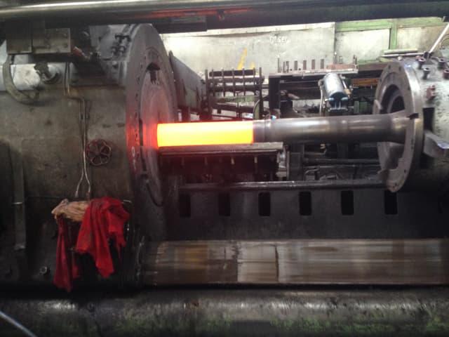 Das glühende Kupfer wird in die Profilpresse gedrückt.